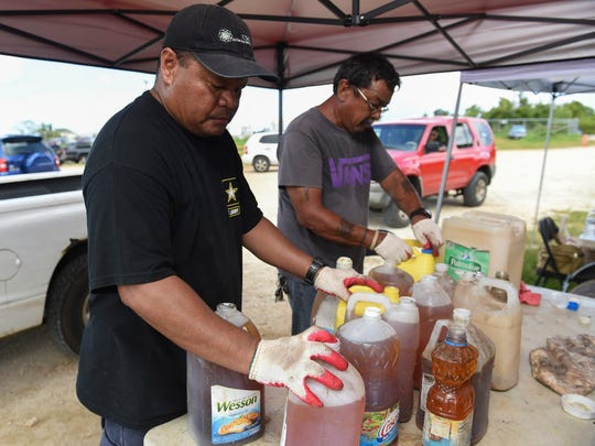Unlimited Services Group workers prepare containers of cooking and motor oil for transportation at the farmers' co-op market and flea market in Dededo on Oct. 28, 2017.
