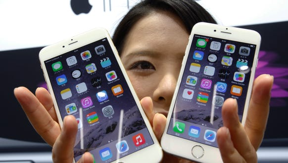 A customer shows off the new Apple iPhone 6 and 6 Plus