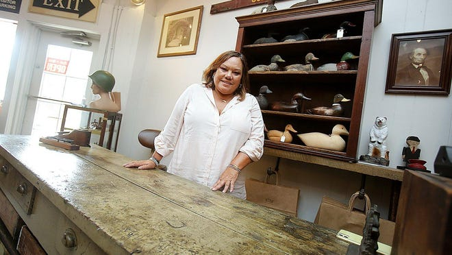 Mary Goff, who owns Antique Revival with her husband, Mike Goff, stands behind an antique country store counter at the corner shop in the Lake Cable Shopping Center at 5555 Fulton Dr. NW. Antique Revival not only has survived, but it has thrived during the coronavirus pandemic.