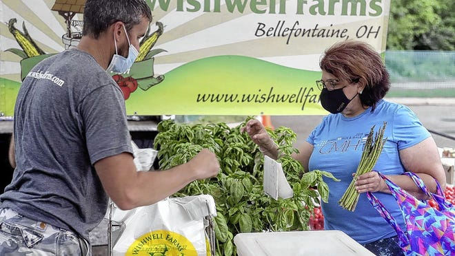 Jason Wish, owner of Wishwell Farms, helps Andrea Tippery of Reynoldsburg browse produce June 4 during the first Reynoldsburg Farmers Market of the season at John F. Kennedy Park, 7232 E. Main St. The farmers market will run 4 to 7 p.m. Thursdays through Sept. 4.