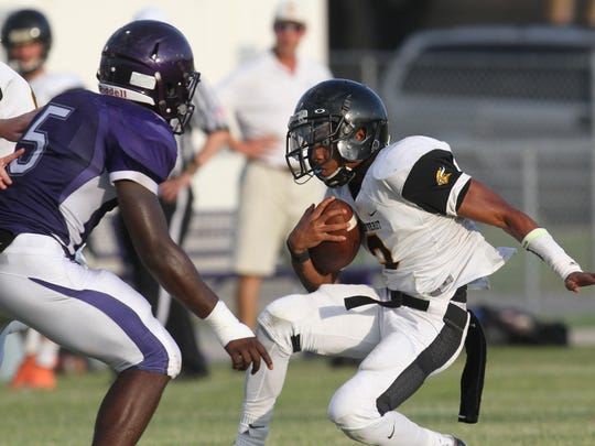 Bishop Verot's KeeShaurn McCaulley attempts to fake out Cypress Lake's Jeff McDonald during a spring football game at Cypress Lake High School on Wednesday.