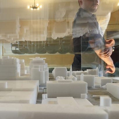 Members of the public view a scale model of the proposed