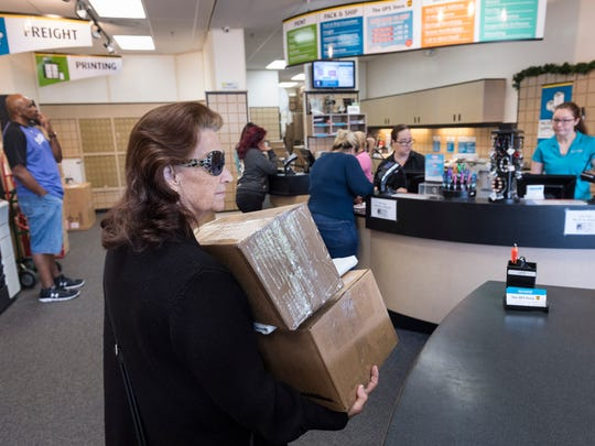 Sheila Marcum waits to ship packages at the UPS Store