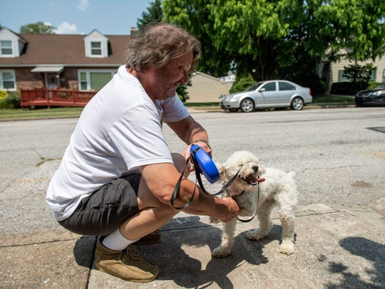 Earl N. Lehman Jr. leans down to untangle his dog,