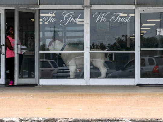 "The ""In God We Trust"" phrase can be seen in the windows of the front doors at Milan High School in Milan, Tenn., in August. Groups that pushed bills to post the national motto in schools are now pushing legislation to require elective Bible classes."