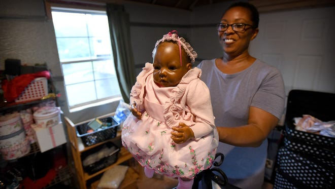 "Certified doll appraiser and doll doctor Valarie Moyer brings memories back to life when she repairs heirloom dolls. From her building at her Jonestown home, Moyer fixes broken and well-worn dolls. Moyer holds a ""reborn"" doll, modeled to look like a real baby."