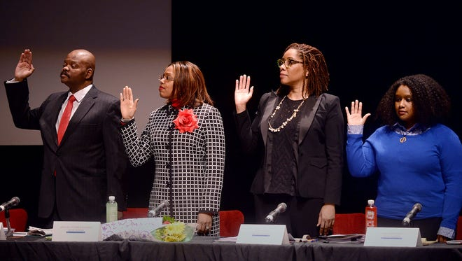 From left, LaMar Lemmons, Angelique Peterson-Mayberry, Sonya Mays and Misha Stallworth raise their hands to be sworn onto the Detroit school board during the swearing-in ceremony on Wednesday, Jan.11, 2017 at Cass Technical High School in Detroit.