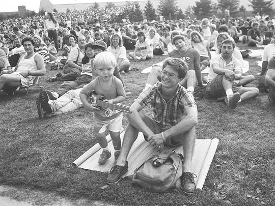 A young concertgoer plays his guitar at the Michigan Festival, Aug. 21, 1987.