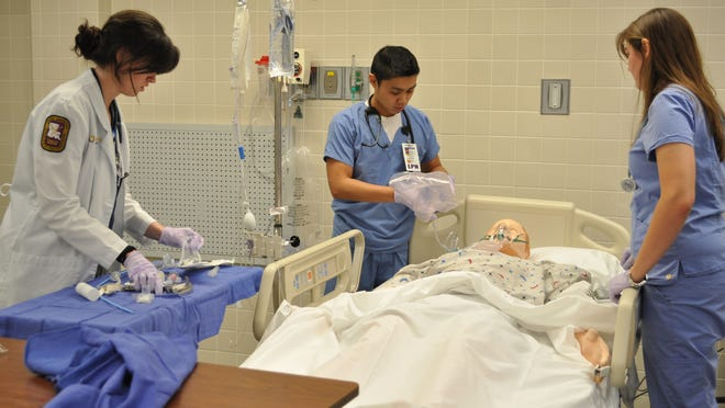 Micah Clauss (left), Jayvee Colarines (middle) and Katelyn Herin (right) respond to a life-like medical situation during the grand opening of Christus St. Frances Cabrini Hospital's new simulation lab.
