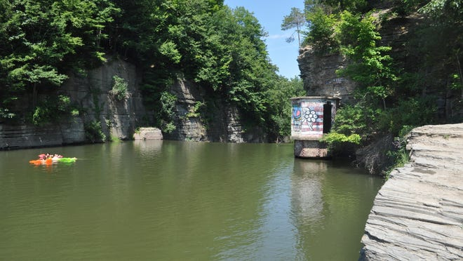 A group of four people float on inflatable rafts and swim while sipping beer around noon on Monday in the popular, but illegal, swimming hole upstream of Second Dam on Six Mile Creek in Ithaca.
