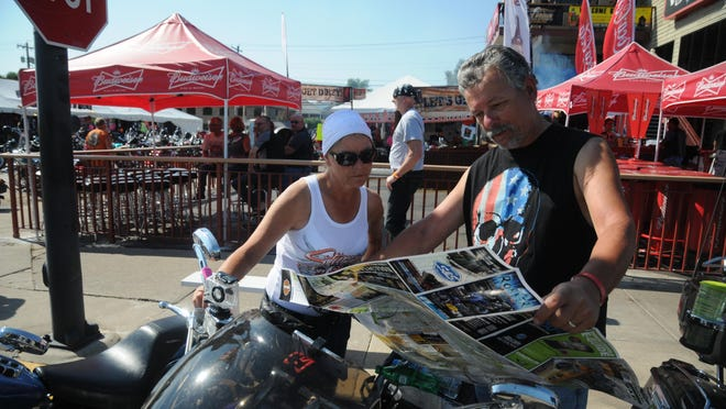 """Sandy Swezy, left, and Tim Swezy, right, traveled from Illinois to attend Sturgis and have explored the Black Hills area. Tim Swezy said on Wednesday in Sturgis, S.D., that it's been on his """"bucket list"""" to attend the motorcycle rally."""