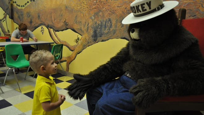 Smokey Bear greets kids at his birthday party held Saturday at the T.R.E.E. House Children's Museum in Alexandria.