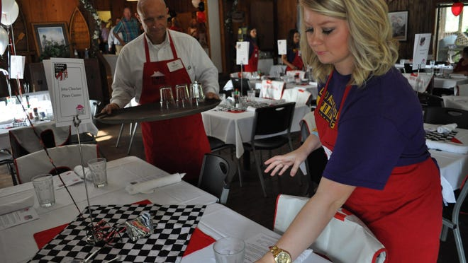 Danee Stanley, a member of the Louisiana State University of Alexandria's pom line, sets tables Sunday for the Hope House lobster dinner fundraiser.