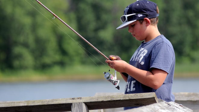 Eric Compton, 12, of Port Huron, puts some bait on his hook Aug. 17 while fishing with his grandpa at 40th Street Pond.