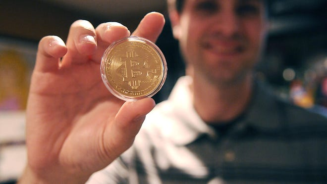 Bitcoin user Jon Zimmer shows his 2013 commemorative bitcoin on Thursday at his home. Zimmer bought the physical memorial because 2013 was his first year trading the currency.