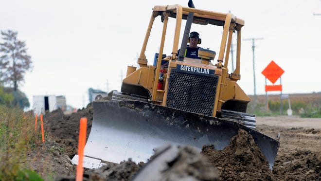 A bulldozer pushes dirt of pipeline thats already been laid Monday, Oct. 5, along Fisher Road in Grant Township.