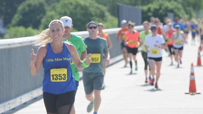 Meg Martin, left, of Poughkeepsie, crosses the walkway during the inaugural Walkway Marathon on June 14.