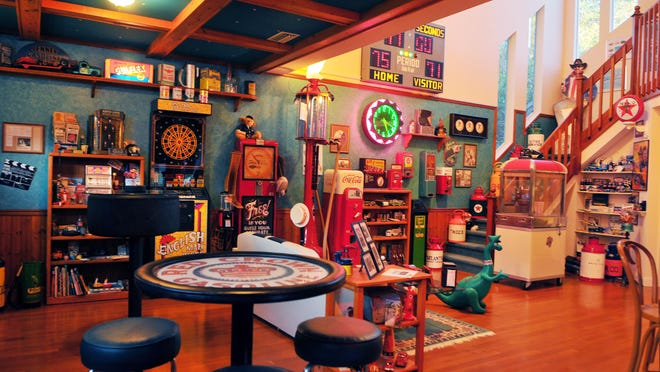 """Walt Kostrzewa's man cave includes immaculately restored gas pumps from the 1920s, classic pinball machines and a couch made from the back end of a Mustang. LEFT: Kostrzewa's """"booze barometer,"""" which was long ago used in bars to check the drunkenness level of patrons."""