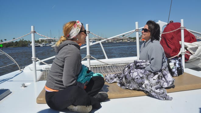 Kelly Dallaire and Angie Torres enjoy the boat ride back to port aboard the Sweet Liberty after doing yoga on Keewaydin Island.