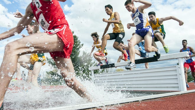 Runners leap over the water during the 3,000 steeplechase event during the America East track and field championships at the Frank H. Livak Facility on the campus of the University of Vermont on Saturday.