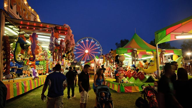 In this archive photo, Tulare County Fair goers walk around the carnival.