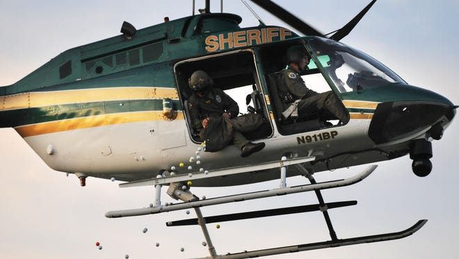 Numbered golf balls are dropped from a BRevard County Sheriff's Office helicopter during last year's Chopper Dropper fundraiser for Florida Tech.