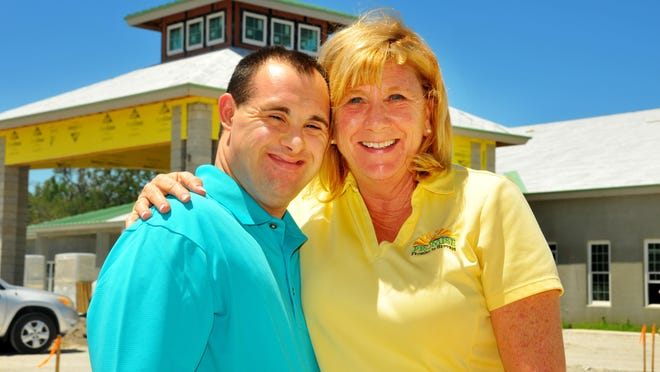 Promise in Brevard co-founders Luke and Betsy Farmer stand in front of Promise the community center at the complex, which will open this fall. Promise is a place where young adults with special needs can live and work.