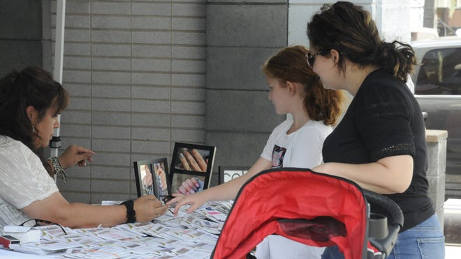 Kendra Hessket looks on as her daughter Josslyn gets helps with press on nail polish from Kelley Hanlon, Color Street Nail Stylist during last Thursday Super Sidewalk Sale in Barnesville