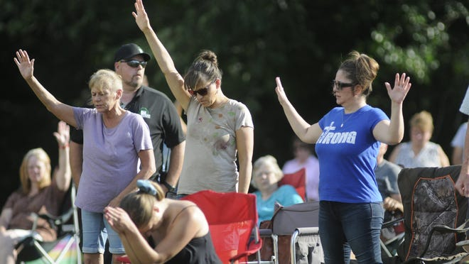 Worshippers react during the Sacred Assembly program sponsored by the Ashland County Ministerial Association at Freer Field on Sunday.
