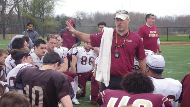 Walsh head football coach John Fankhauser addresses his team during a spring game.