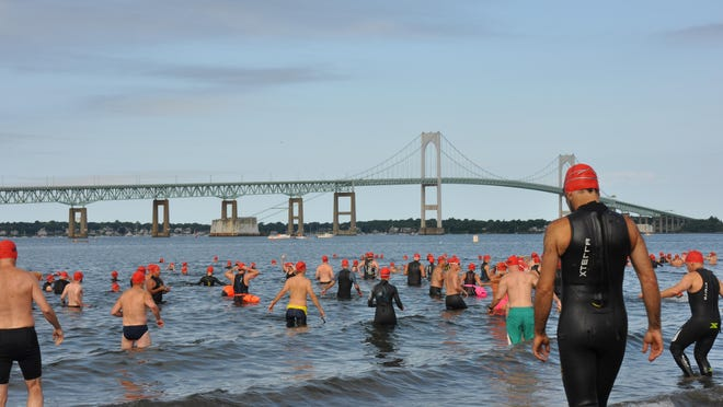 Swimmers make their way into Narragansett Bay for the 2019 Save the Bay Swim. Because of the coronavirus pandemic, this year's swim will be replaced by a virtual event that will also involve running, biking and paddling on kayaks and paddle boards.