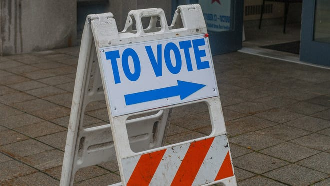 A sign points voters to the entrance of the Cambridge Water Department polling place, one of three early voting locations in Cambridge.