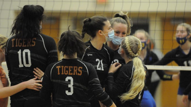 The Hudson volleyball team celebrates after winning a point in the first game of Thursday night's Division 3 district final against Madison. The Tigers defeated the Trojans in straight sets 25-15, 25-12, 25-16 to advance to next week's regional round at Madison.