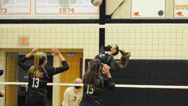 Onsted's Kennedy Ross (2)  hits a kill attempt against Hudson's Callie Bauer (13) and Ally Deline (19) during their Lenawee County Athletic Association match Tuesday night in Hudson. Telegram photo by Deloris Clark-Osborne