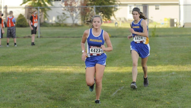 Madison's Kiersten Brackleman, left, and Brook Fetter run towards the finish line during Tuesday's Madison Invitational. Brackleman and Fetter led the Trojan girls team picking up the team title on their home course.
