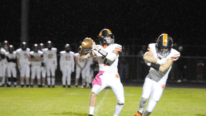 Hudson's Dylan Smith (2) sets to throw the ball on a two-point conversion attempt during the Tigers' 41-7 victory over Onsted on Friday night.