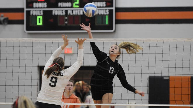 Hudson's Callie Bauer (13) tips a ball over the hands of Vandercook Lake's Anna Macomber (9) during their Division 3 regional final last November at Leslie High School. Bauer, the two-time defending Lenawee County Player of the Year, looks to lead the Tigers back to another deep postseason run as the season gets underway Thursday.