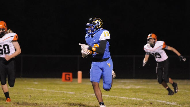 Madison's Rovahn Roberts runs with the ball after an interception during Friday's game against Quincy.