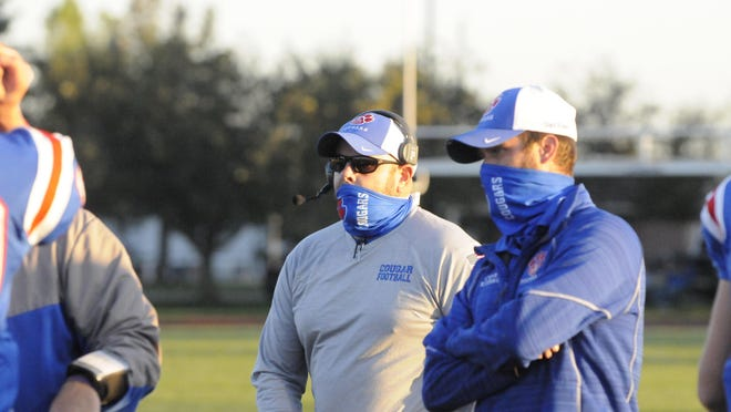 Lenawee Christian head football coach Bill Wilharms (middle) looks to the sideline before a game in the 2020 season.