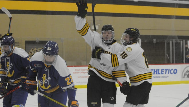 Adrian College's Rex Moe and Connor May (18) celebrate after Moe scored in the first period of the Bulldogs' game against Lake Superior State on Nov. 29, 2020.