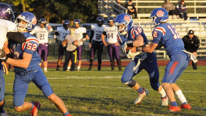 Lenawee Christian's Jameson Chesser takes the handoff from Landon Gallant during Friday's game against Athens.