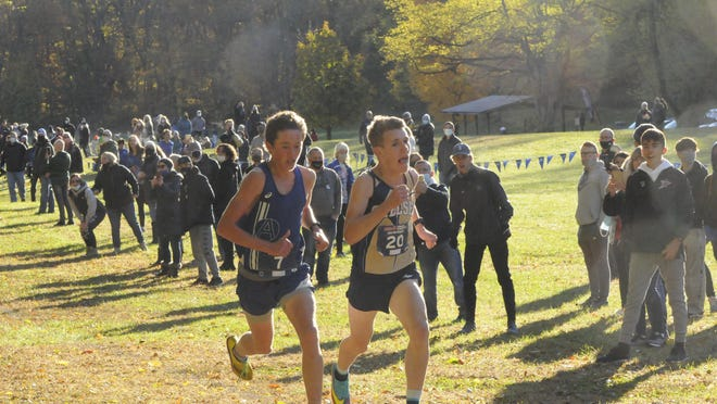 Adrian's Aiden Smith, left, races Chelsea's Connor Alford to the finish line at Saturday's Division 2 Pre-Regional meet at Heritage Park. Smith picked up the victory in a photo finish, coming across the line in a time of 16:46.33 to Alford's 16:46.34.