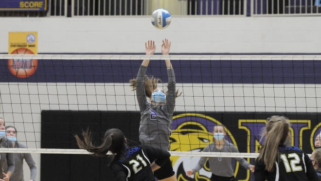 Onsted's Kennedy Ross (2) leaps to block a kill attempt by Madison's Calie Sower (21) during the championship match of Saturday's Lenawee County Tournament at Onsted High School. Onsted will look to defend its home court again as it hosts a Division 2 district, while Madison goes to a district full of county teams in the Division 3 district at Hudson.