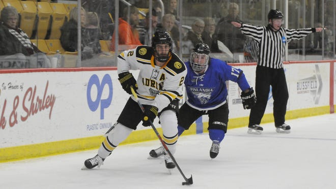 Adrian College's Matt Eller (2) controls the puck as Finlandia's Zach Erhardt (17) chases him during a game on Nov. 15, 2019 at Arrington Ice Arena.