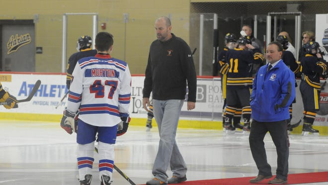 Tecumseh Public Schools athletic director Jon Zajac, center, participates in a ceremonial puck drop at the first game of the Lenawee United hockey team, Nov. 22, 2019.