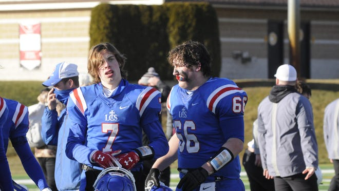 Lenawee Christian'sJoey Breckel (66) and Tyler VanEtten (7) walk off the field and Adrian College after beating Martin in the Diviosn 1 8-Man state semifinal on Saturday, Jan. 9.