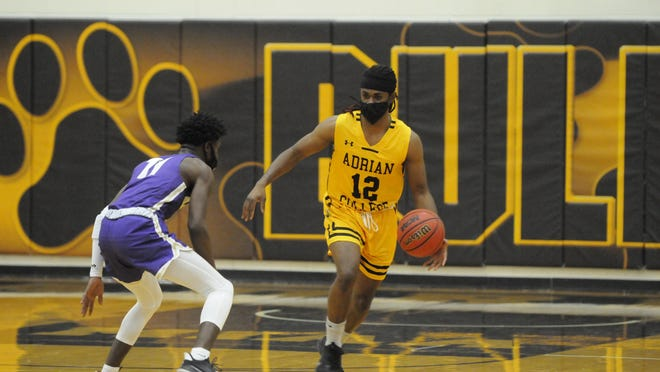 Adrian College's Victor Sheffey (12) brings the ball up court against an Albion defender during their game on Saturday afternoon.