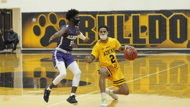 Adrian College's Tyler Gillery (2) moves with the ball as Albion's Devin Holmes (14) defends during Saturday's game.