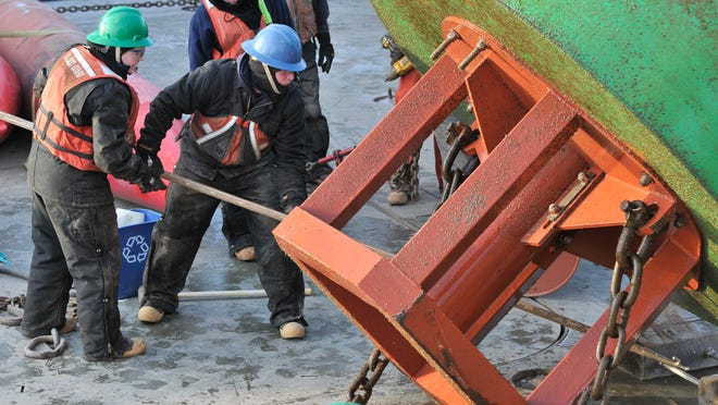 Two crew members position the blocks under the summer buoy on the deck of the U.S.C.G.C. Hollyhock Saturday, in southern Lake Huron.