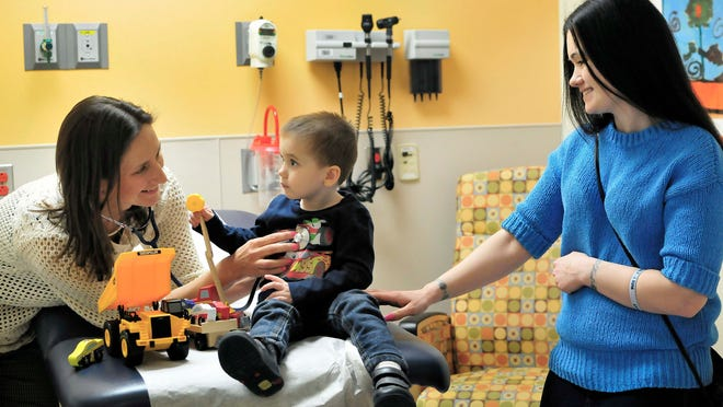 Dr. Giselle Sholler meets with Kat Musgrove and her son Kian, 3, at DeVos Children's Hospital. Kian's cancer is in remission and is receiving medicine to help prevent a relapse.